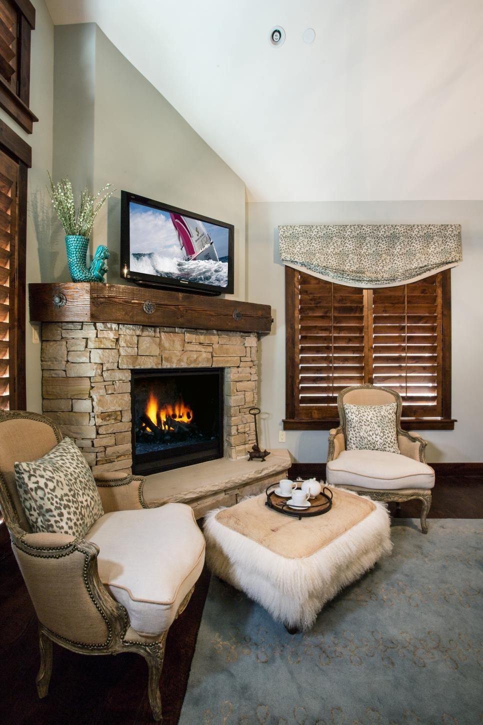 This cozy master bedroom features a stone fireplace which designer