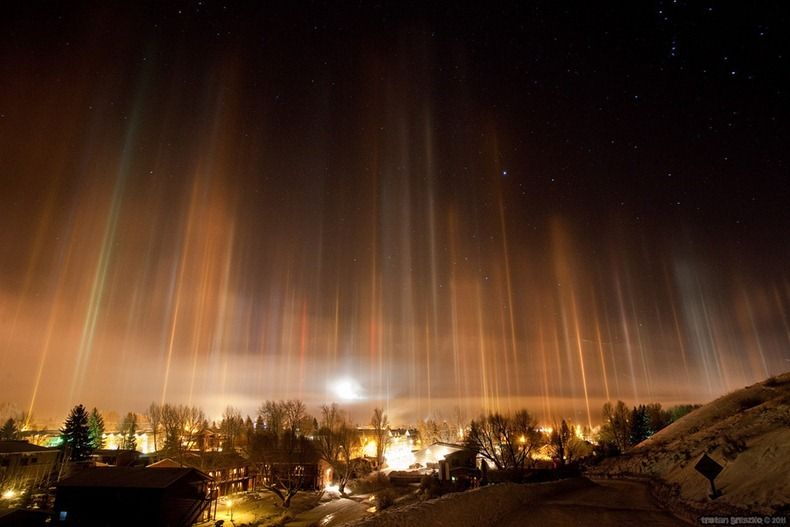 """Light pillars appear when artificial light or natural light bounces off the facets of flat ice crystals wafting relatively close to the ground. When the light source is close to the ground, the light pillar appears above the floating crystals. When the light comes from the sun or moon, the light pillar can appear beneath them, too, as the light refracts through the crystals."""