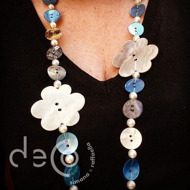 collana lunga con bottoni in madreperla, bianchi e azzurri e due grandi giorni anch'essi in madreperla, indossata
