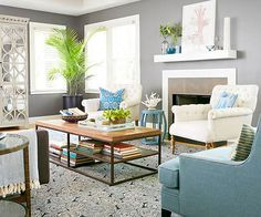 Bluebird + Gunmetal + Snowy White Cool gray walls paired with plenty of blue captures a modern tone in this living room, which is enhanced by contemporary furniture and accessories. Using soft white, rather than a stark shade, injects the space with warmth, as does the wood coffee table top and touches of nature./