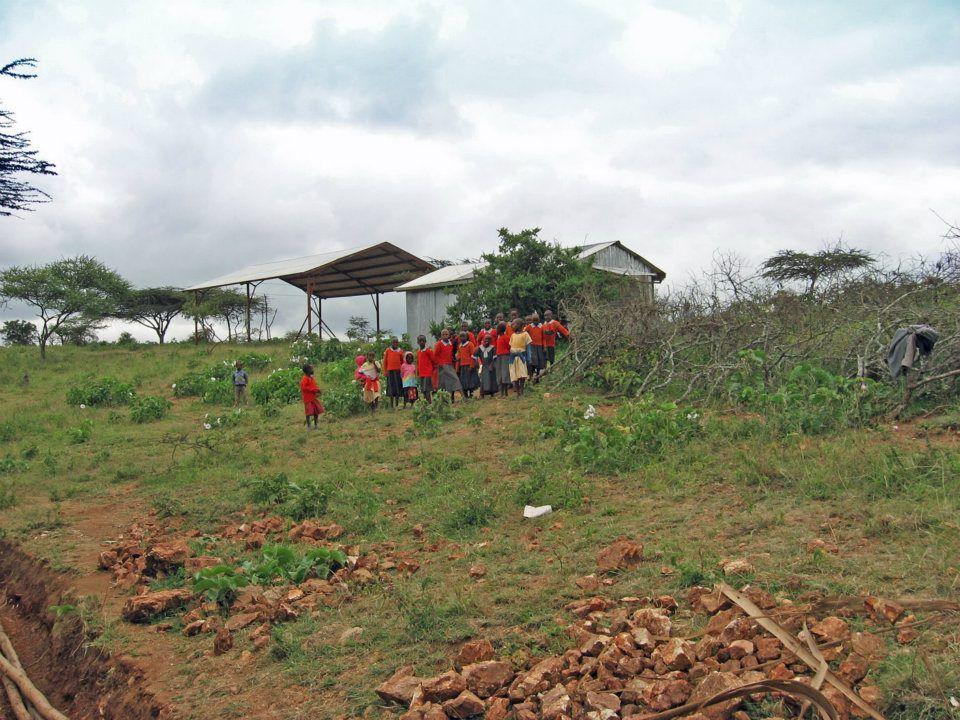 Children from Bisil school watch construction of the chicken coop during a break!