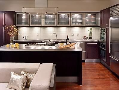 Stainless steel countertops and upper cabinets echo the top-notch  appliances to create a clean, contemporary kitchen design. Dark wood  cabinets help to ...