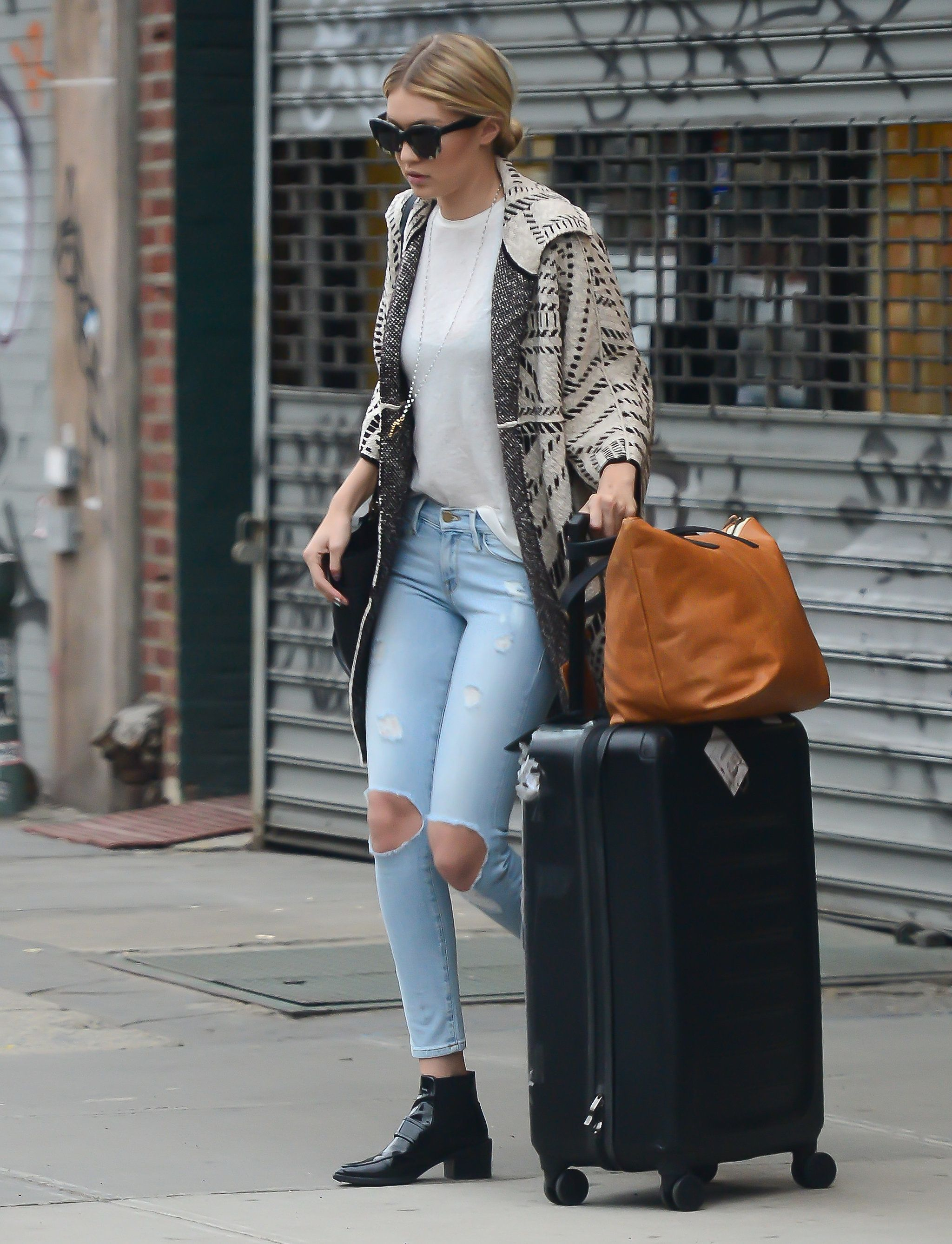 69a3eca1e21 The model had the perfect travel look when she headed out in a sweater coat  and distressed jeans