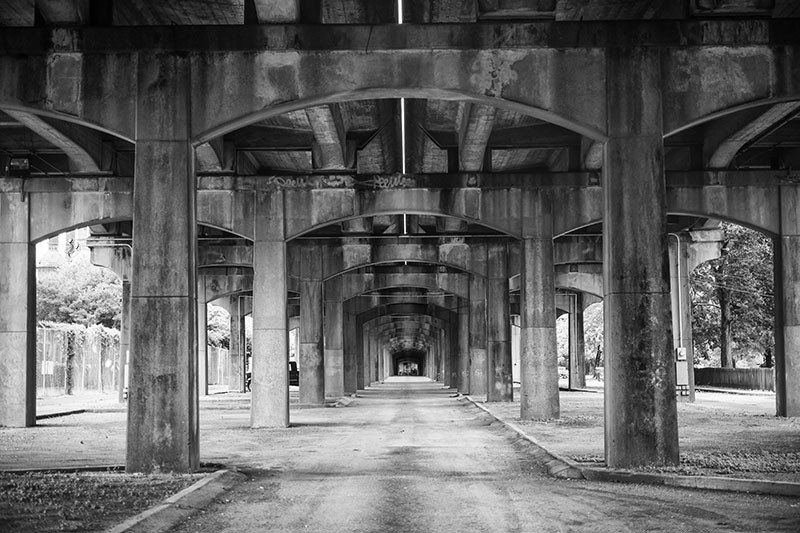 Black and white photograph under the 1st avenue north bridge that runs past the sloss furnaces in an industrial area near downtown birmingham alabama