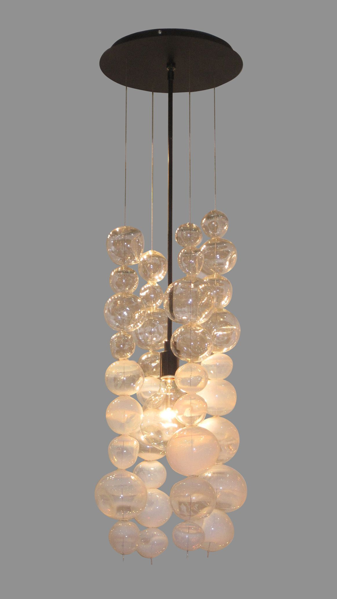 The Dimpled Ball chandelier assembles multiple hand-blown spheres which are sculpted at the furnace with a dimpled, organic form. The chandelier plays upon the interplay and sparkle of these assembled forms as light scatters through them.