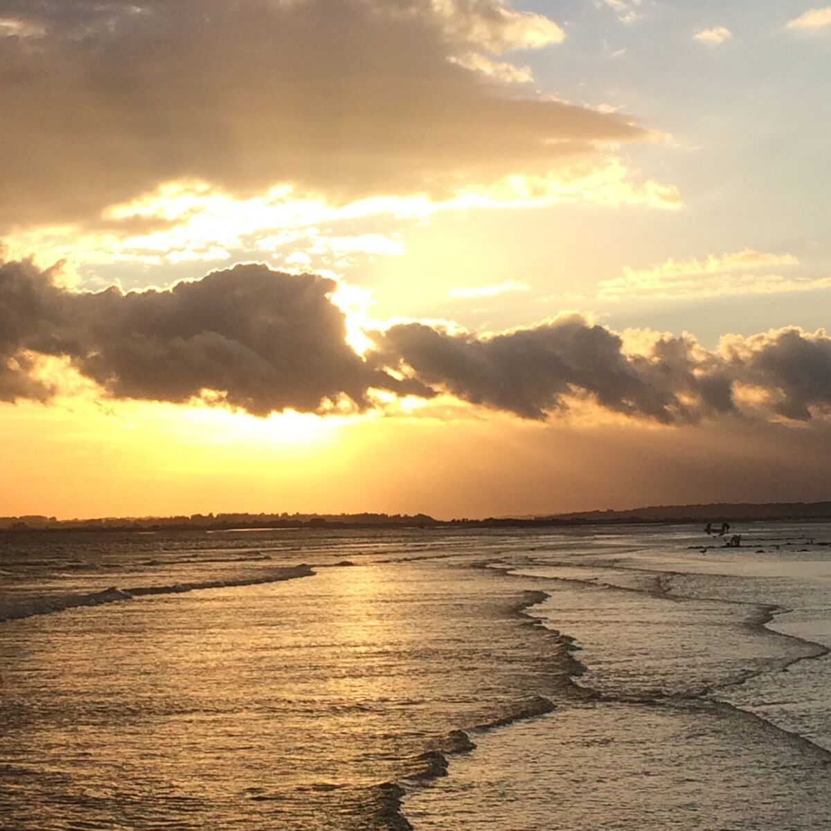 In coming tide as the sun sets over Camber Sands beach
