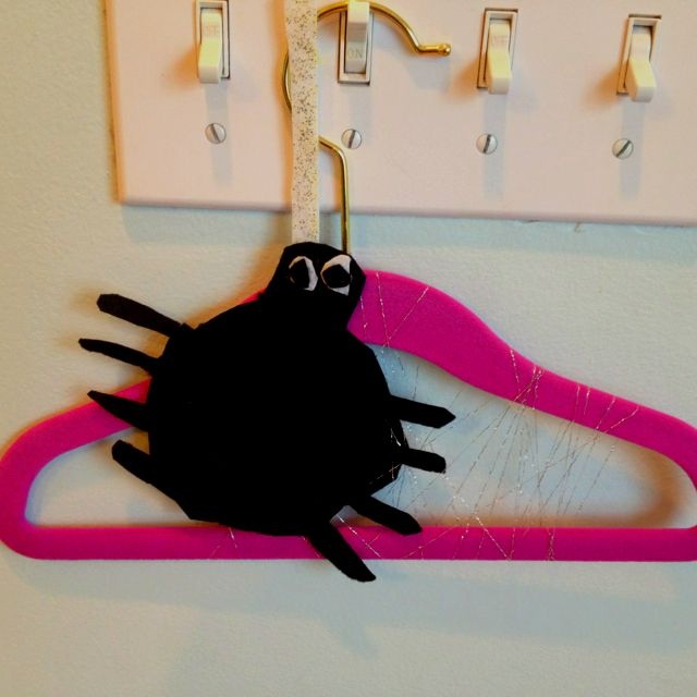 """Cute Halloween decoration! Felt spider cutout attached to a hanger with a """"web"""" of frays from old ribbon. Created by a first grader :)"""