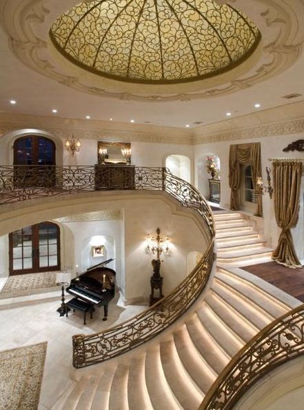 A spacious foyer with a domed ceiling and double staircase makes a ...
