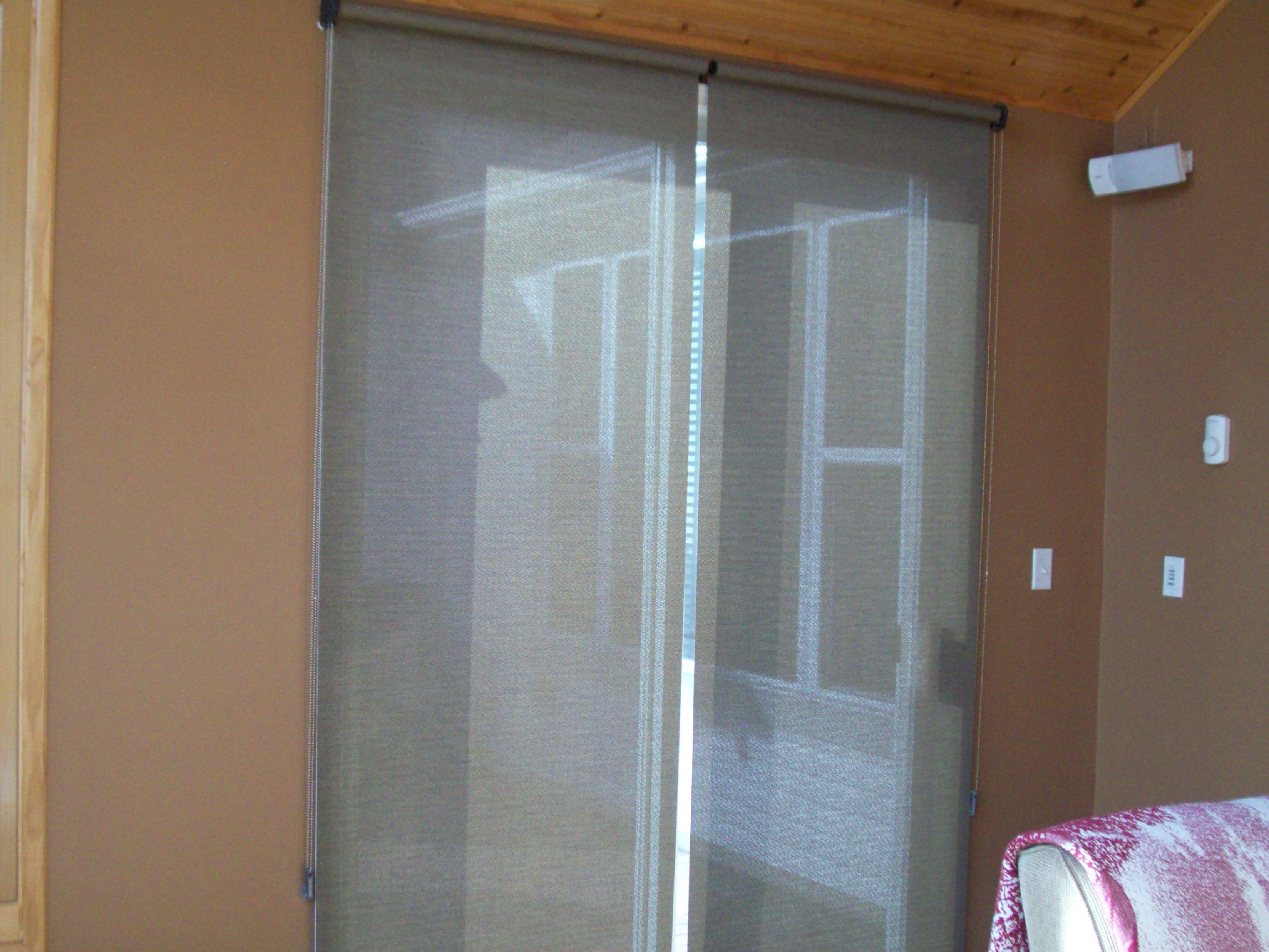 2 Sun Screen Shades Butting Together On A Patio Door