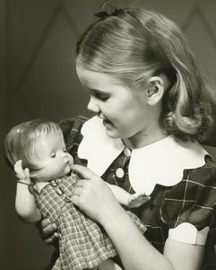 Vintage photo of a little In 1934, the Ideal Novelty and Toy Company produced what was to become one of the top-selling dolls during the Depression Era — the Shirley Temple doll. Designed by Bernard Lipfert, the doll was a faithful likeness of the six-year-old film star, right down to her trademark dimples and blonde corkscr...girl with her doll.