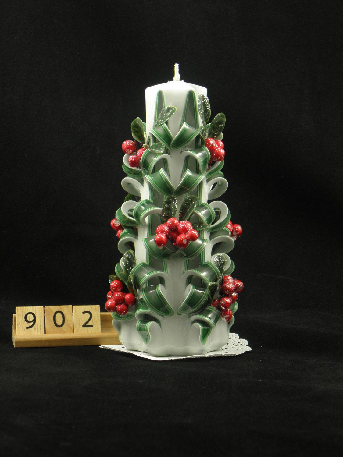 Beautiful carved candle with unique design looks like on the small Christmas tree.