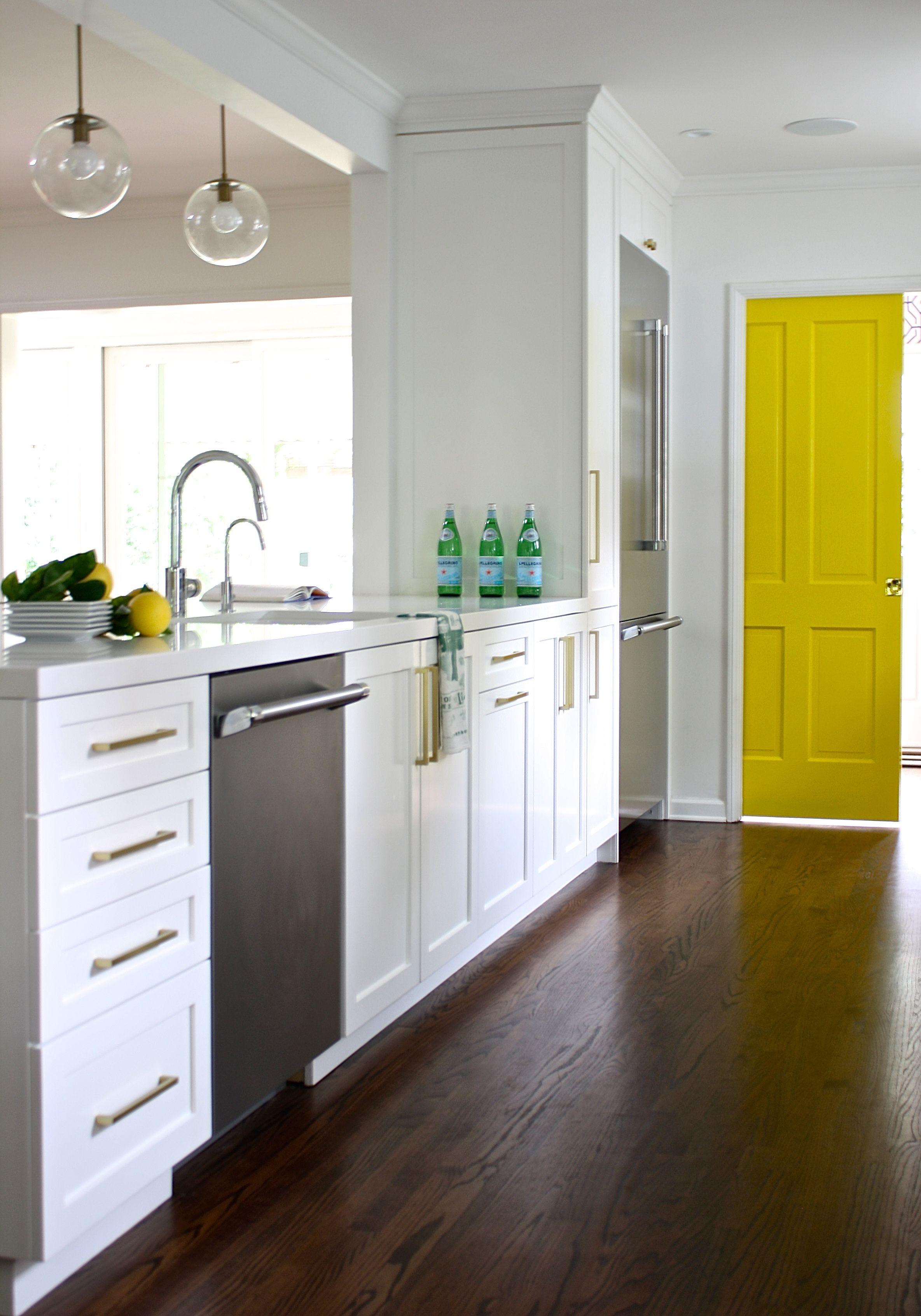 white kitchen shaker cabinet brass pulls yellow pocket door