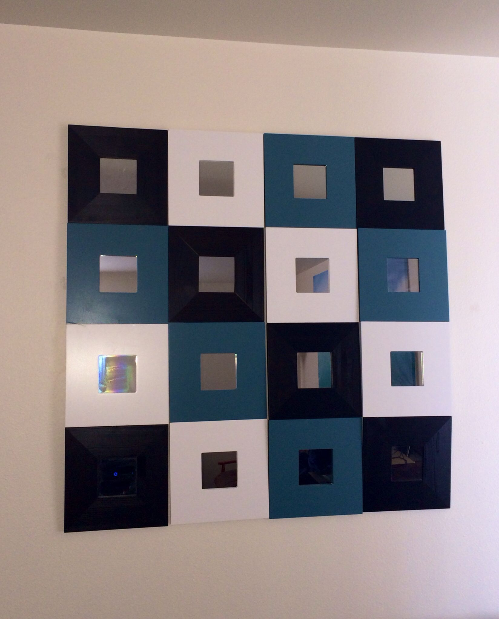 IKEA malmas mirrors using only 4 nails. It's  decent sized wall decor for only $1.99 per mirror!  I used duct tape to tape the 4 mirrors together. All three colors are stock from IKEA but you could paint them any color.