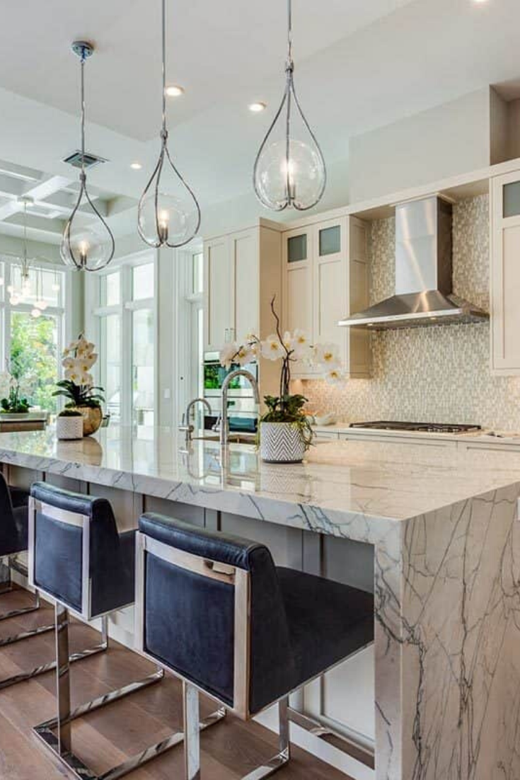 Elegant, bright and airy kitchen design. The interior includes a luxurious waterfall style marble center island and delicate pendant lights which complement the modern rustic cabinets and textures backsplash.  #kitchen #kitchendesign #kitcheninterior  Source: Architectural Designs