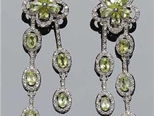 Pendientes largos en montura de plata de ley, decorados con peridotos, talla oval, en garras, con forma de flor calada con circonitas. 54 mm.