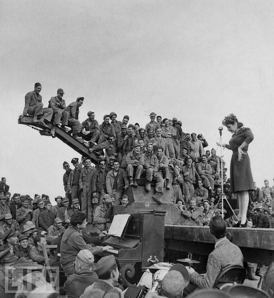 Martha Raye on stage before a rapt audience of servicemen during a 1943 USO tour in North Africa.