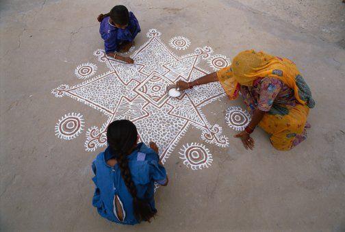 ndia, Rajasthan, Tonk, women drawing mandala on ground, elevated view Credit: Bruno Morandi