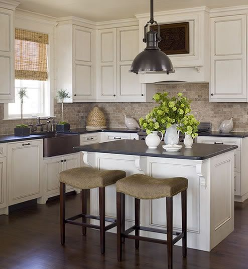 Dark hardwood floors with antique white cabinets Ivory kitchen