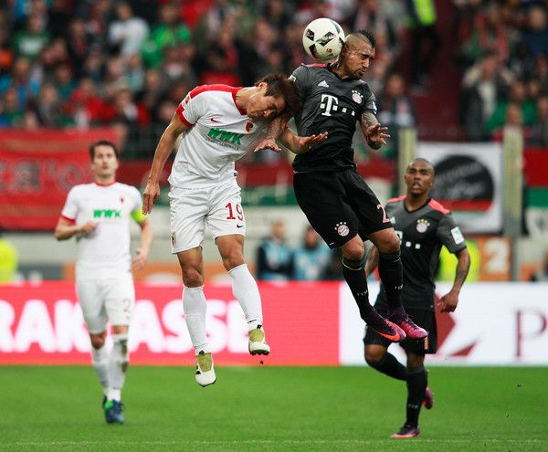 Arturo Vidal of Bayern Munich is challenged by Koo Ja-Cheol of Augsburg during the Bundesliga match between FC Augsburg and Bayern Muenchen at WWK Arena on October 29, 2016 in Augsburg, Germany.