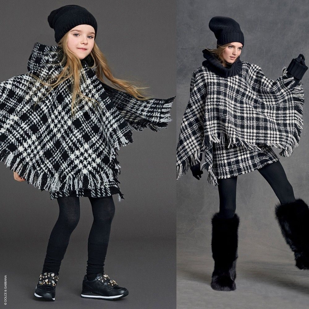 Girls beautiful black and ivory houndstooth check cape by<span>Dolce & Gabbana made from a thick knitted wool. Unlined, it has an attached hood and fastens at the front with concealed poppers. Finished with a tassel trim this is a great alternative to a jacket or coat worn over a top or sweater.<br /></span> <ul> <li>99% wool, 1% elastane (thick knitted feel)</li> <li>Dry clean</li> <li>Large cape</li> <li>Concealed zip fastening</li> <li>Comes with cotton bag</li> <li>Design taken...