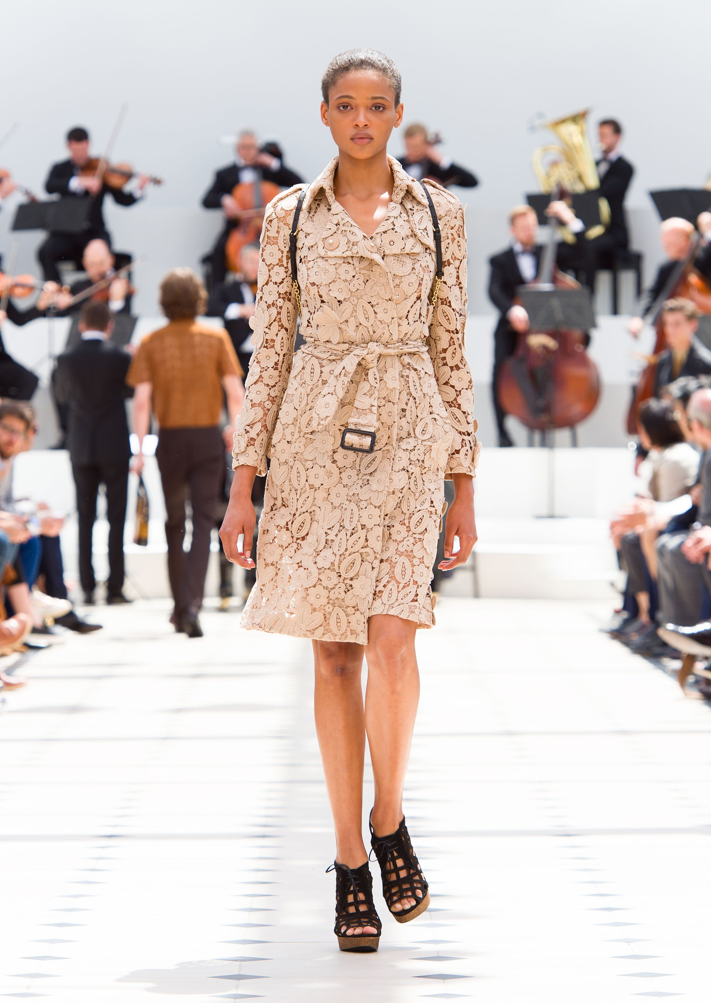 A nude trench coat in floral macramé lace and The Bucket Backpack
