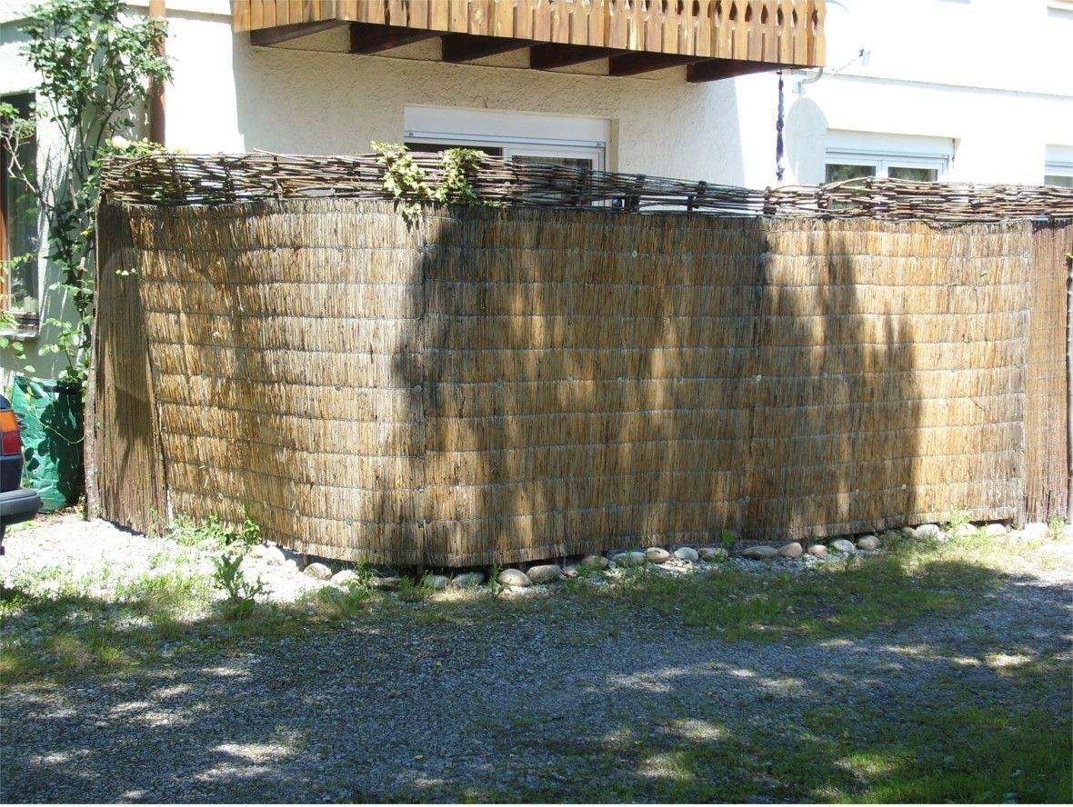 Sichtschutz aus Strohmatten mit Weidengeflecht als Abschluß