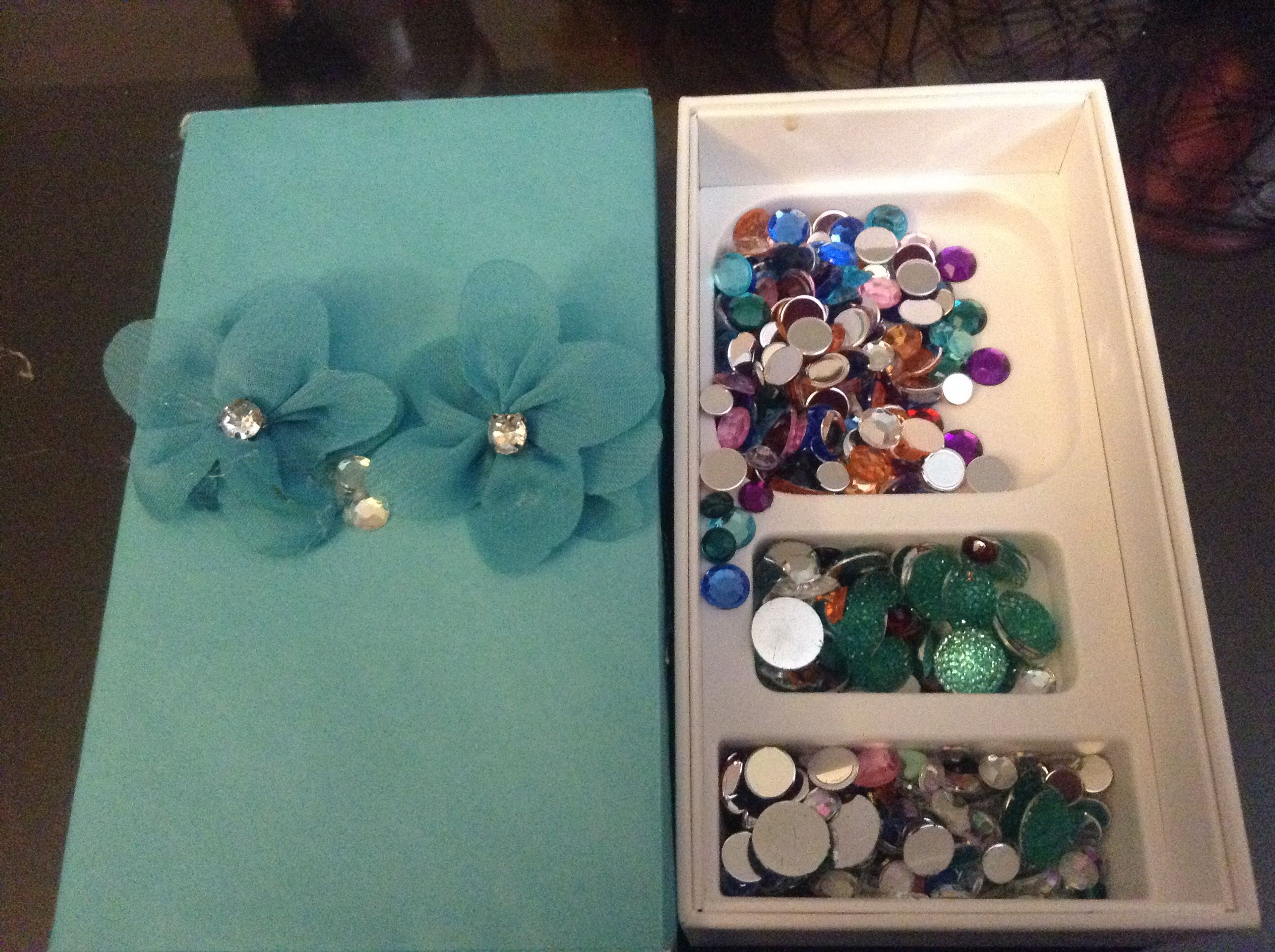 My newly upcycled iPhone 5 box that now holds my sequins and glass beads. I covered the box with a blue envelope that was hanging around the house. After that, I glued the little blue flowers and rhinestones onto the front of it.