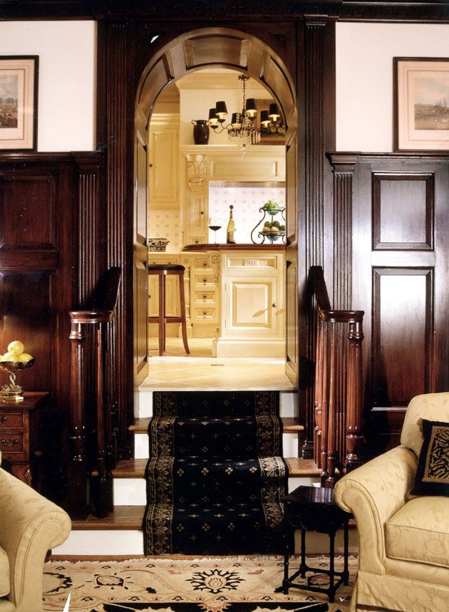English Paneled Room: Dark Wood Panel Walls Leading To White Kitchen