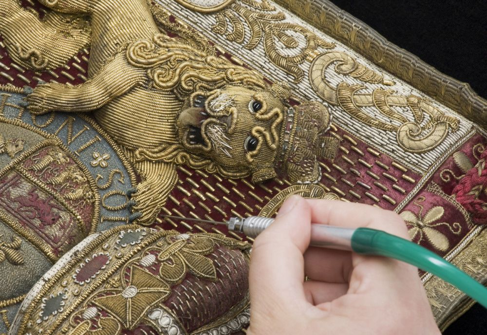 Using a micro vacuum cleaner to clean the Ickworth Privy Purse at the National Trust Textile Conservation Studio. ©National Trust Images/John Hammond.