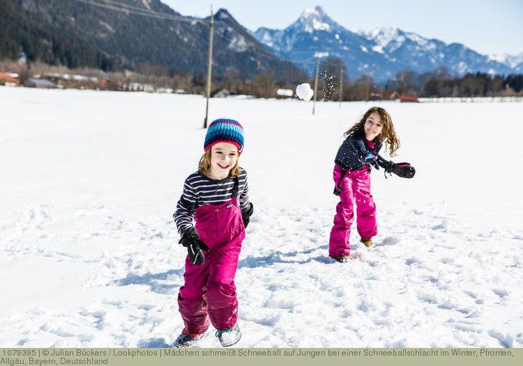 Mädchen schmeißt Schneeball auf Jungen bei einer