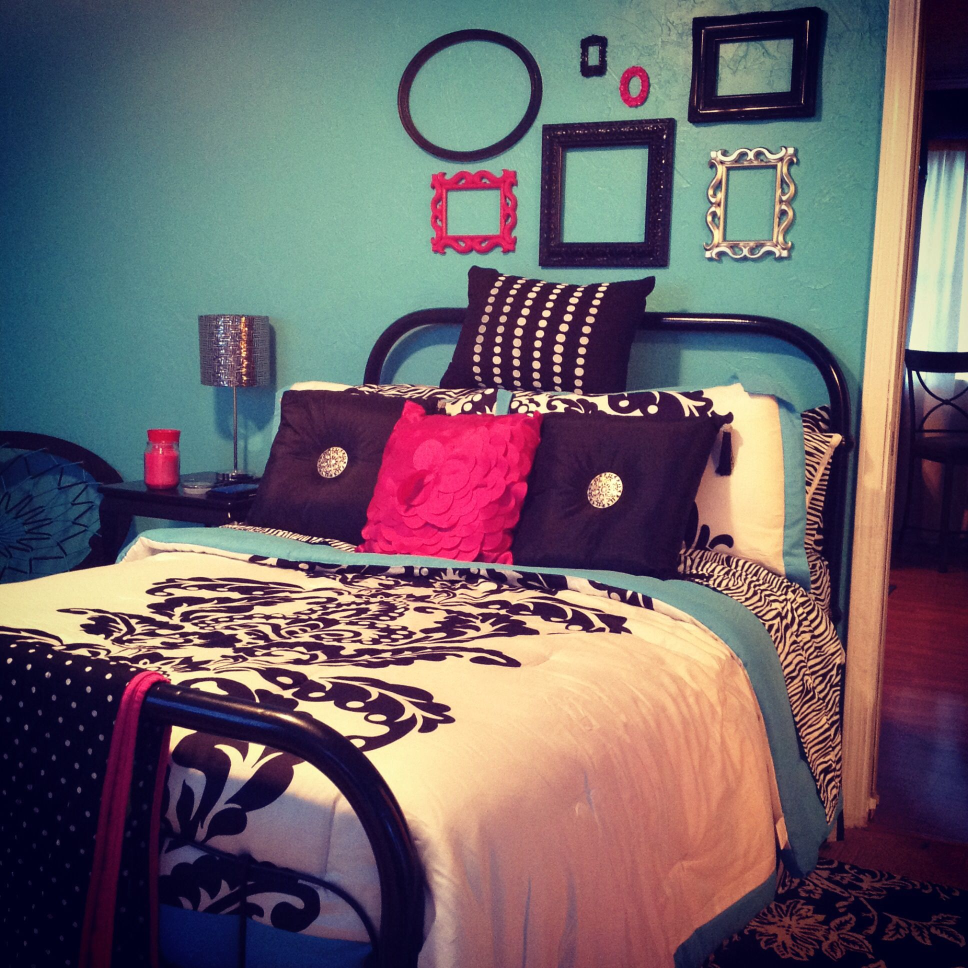 My bedroom :). Turquoise, white, and black with a berry pink accent. So chic! Bedspread from Walmart and accent pillows from Ross. Frames on the wall from Goodwill and Kirklands. The spring chair in the back from Target! Lamp is from Gordman's