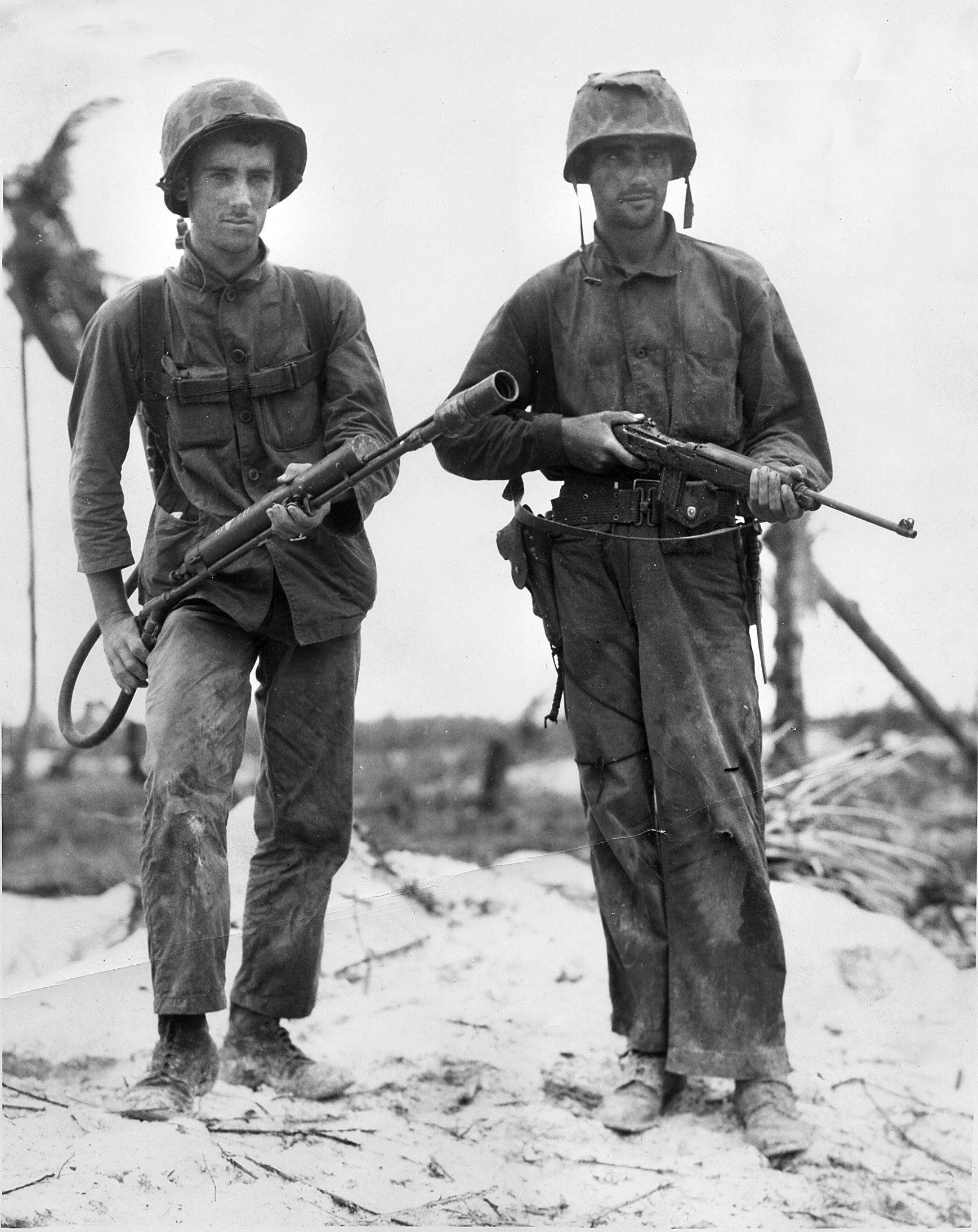 "US Marines Stanley A. Parks (left) and Randolph Peters pose for the camera with the M1A1 Flamethrower and a M1A carbine, Peleliu, 1944. Compare and contrast their overall appearance with that of cinema ""heroes"" of the 50s and 60s -- pressed dungarees, clean shaven faces, perfectly laced boots, and polished helmets. Reality vs make-believe."