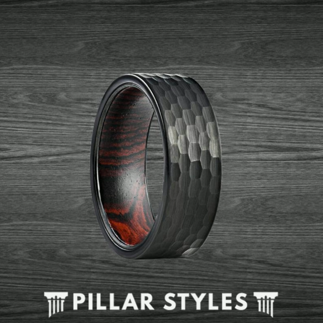 Exotic wenge wood lines the inside of this black hammered tungsten ring to create a bold, masculine wedding band! The ultra-durable 8mm tungsten carbide has a brushed black finish that complements the dark wenge wood grain patterns perfectly.  #mensfashion #mensweddingband #weddingring #mensweddingring #weddingband #mensweddingbands #woodring #l4l #c4c #weddingrings #menweddingring #tungstenrings #weddingbands #damascusring #like #follow  #weddingring #damascussteelring #uniquering #pillarstyles