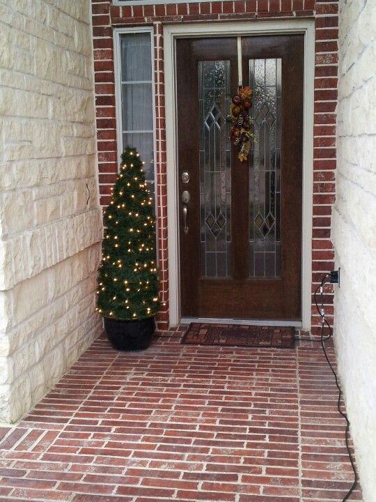 Christmas tree made for porch from tomato cage, garland, and lights! Way cheaper than buying!