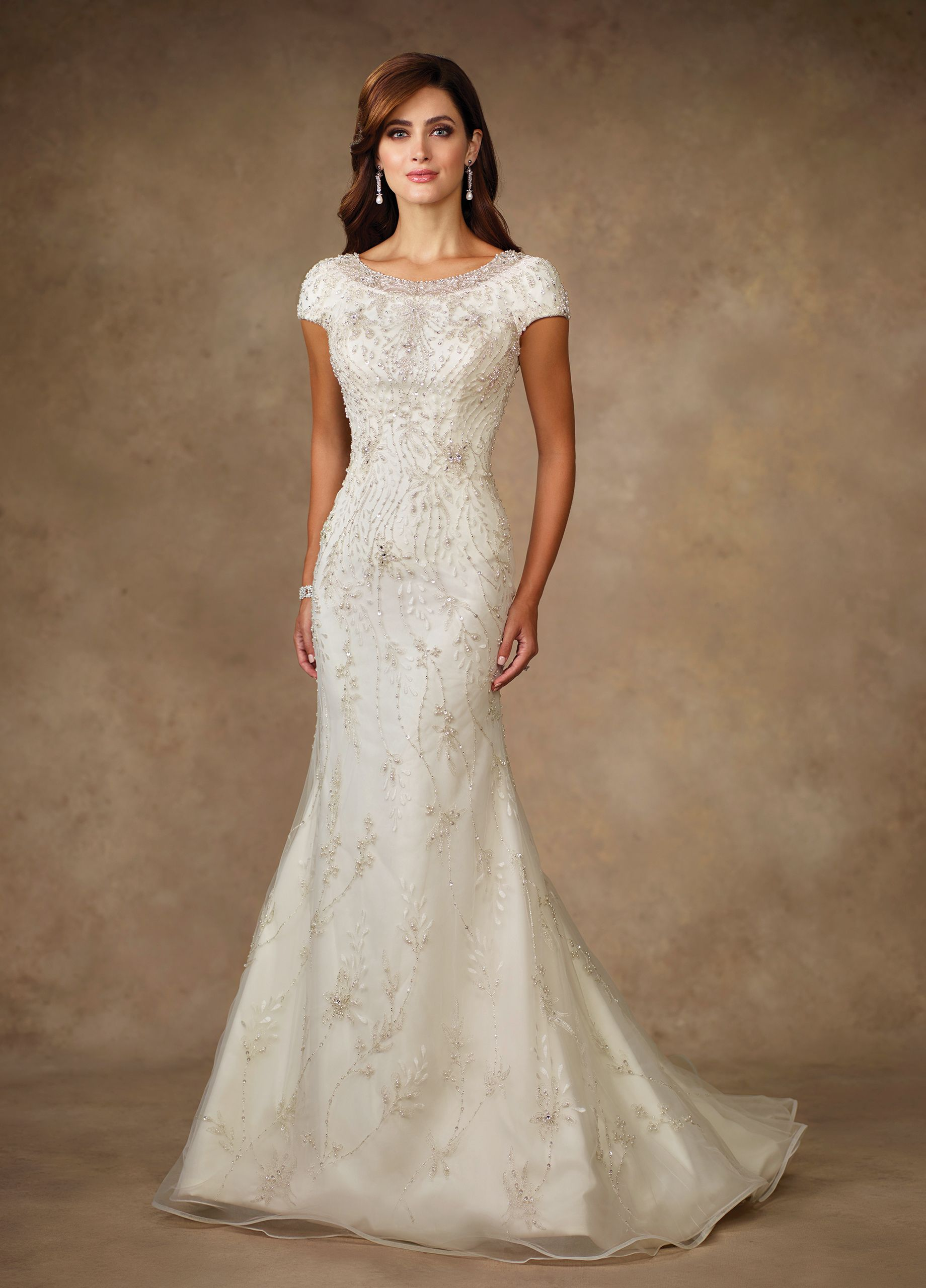 TR11706 - Hand-pattern beaded and embroidered motif on tulle over organza and soft satin trumpet gown with cap sleeves, front and back bateau necklines trimmed with elaborately hand-beaded illusion, dropped waist, covered buttons down back, chapel length train.