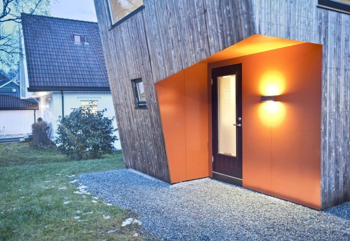 L'ingresso di casa, protetto dal volume sporgente, risulta definito da una vivace colorazione arancione