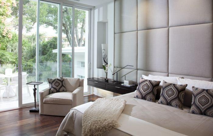 Wandverkleidung, Doppelbett mit Musterkissen, weißer Sessel mit