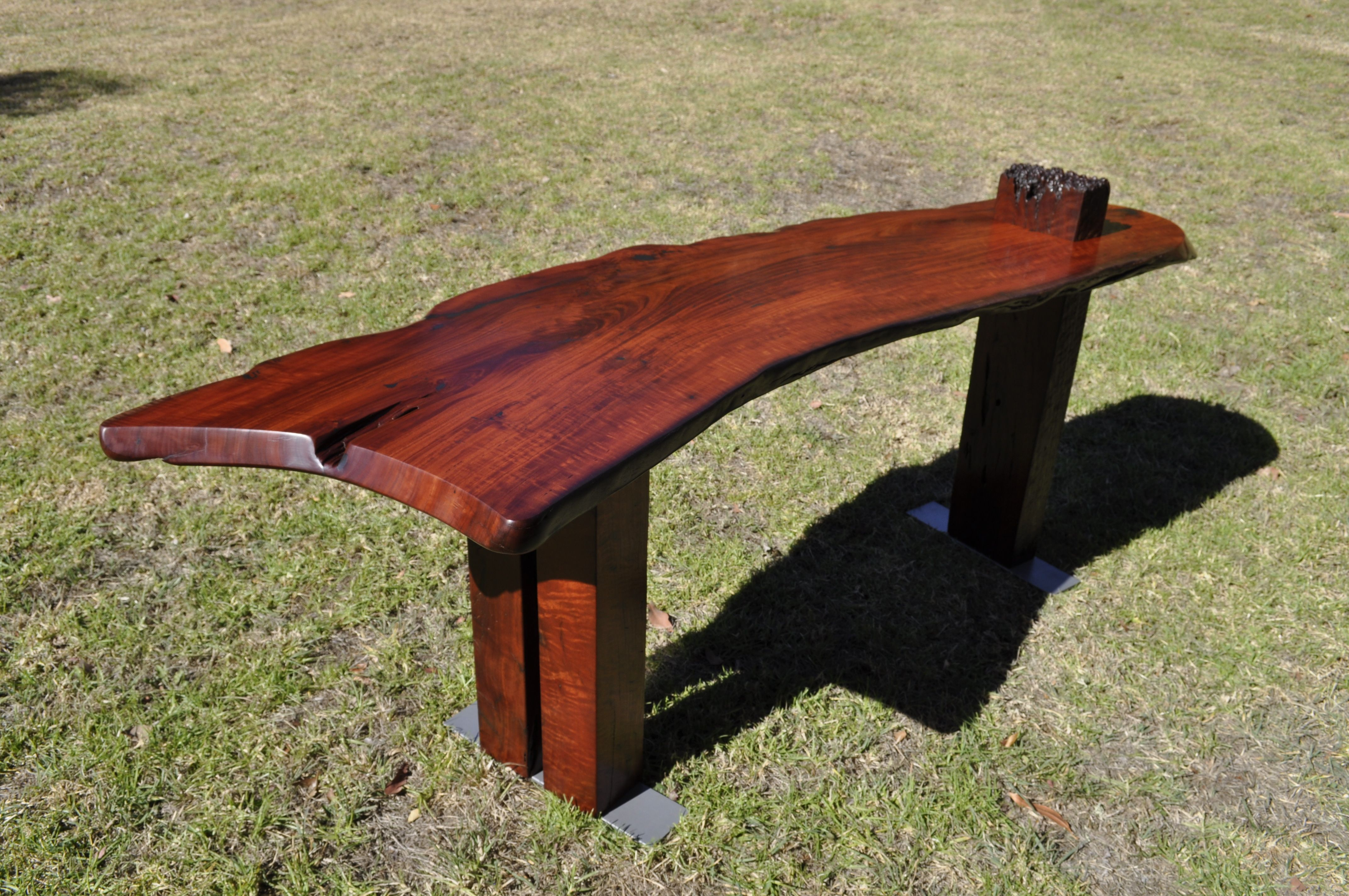 'Live Edge - Boomerang' - This single slab of Redgum in my opinion resembling the shape of a boomerang, has natural live edges and has been finished in a burnishing process with an all natural tung oil mix.   The legs are old salvaged fence posts and recycled steel for the base, with visible pitting on the steel from the years exposed to the elements. The weathered salvage fence post protrudes through the #desk top for a bit of a cool feature. Warning: This table if thrown may not come back!