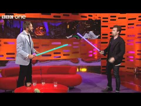 Ewan McGregor, Graham Norton, and Chris O'Dowd turn off the lights and play with light sabers. I love the way Ewan shrugs when Graham tells him how much they cost.