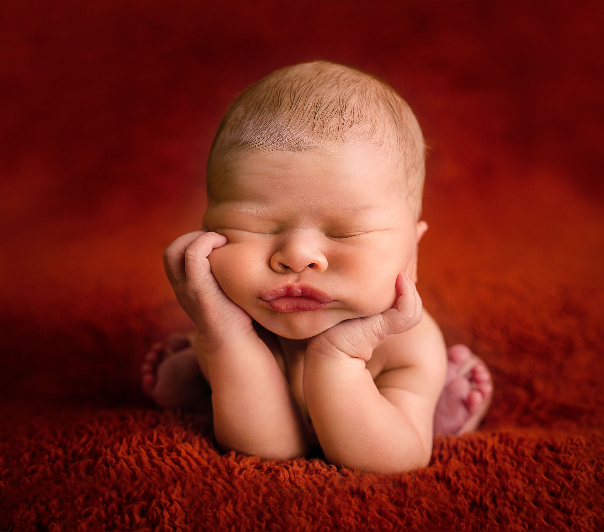 Newborn baby in froggy pose with pouty lips on red background