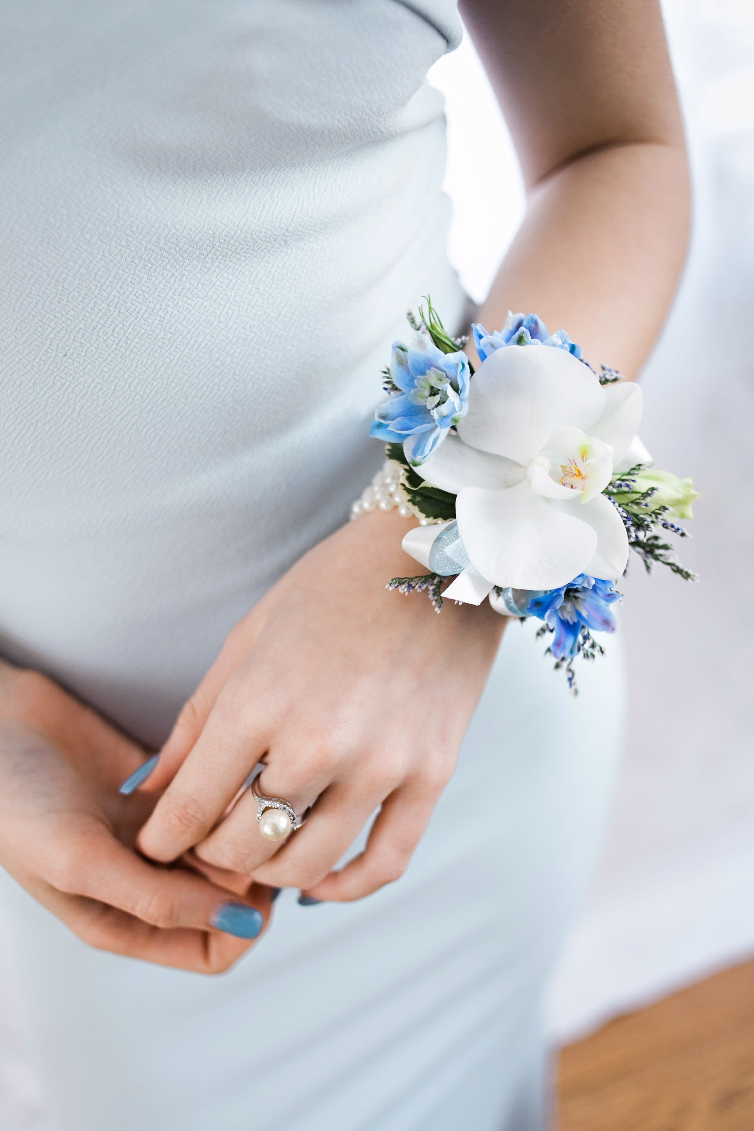 White orchid and blue delphinium corsage on a pearl