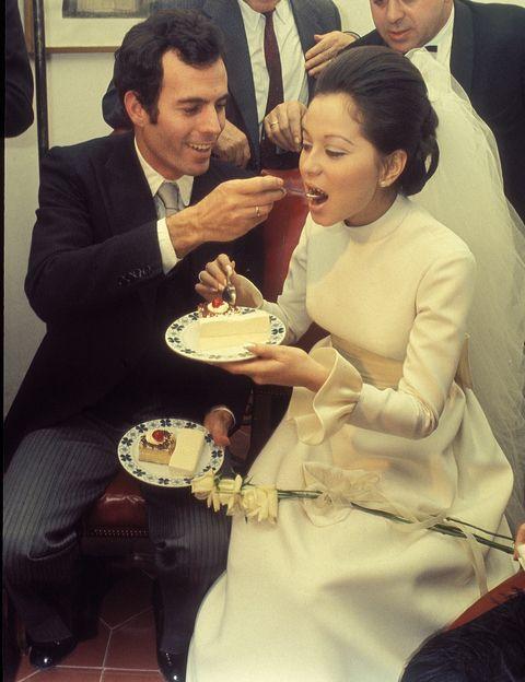 Isabel Preysler - Su enlace con Julio Iglesias fue el gran bodorrio de los años 70. Lució un vestido de manga larga con fajín en color champán, con volantes y cuello alto. El pelo lo llevaba recogido en un moño de donde prendía el velo.