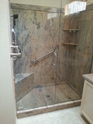 Slab wall shower with seating, storage, and an assist bar.