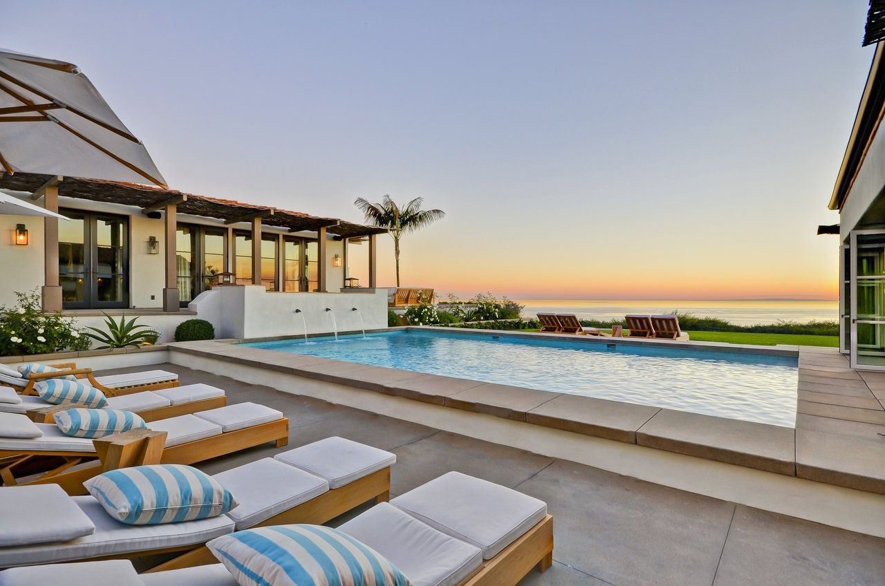 Captured great backyard ideas from this incredible dream home patio. Beautiful breath-taking ocean views, a custom inground pool perfect for swimming and entertaining, comfortable and relaxing, laid back white beach chairs with baby blue and white stripe pillows.