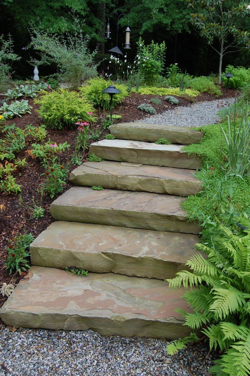 The natural stone steps of a stairway garden feature climb a small - Stone Boulder Steps Gravel Path