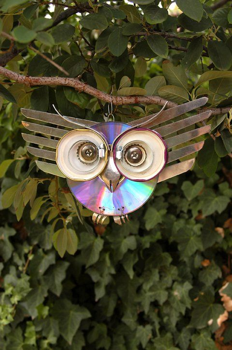 This kitchen owl was made from salvaged kitchen supplies and a  CD which is reflective and can help keep away hawks or other birds from your veggie garden.