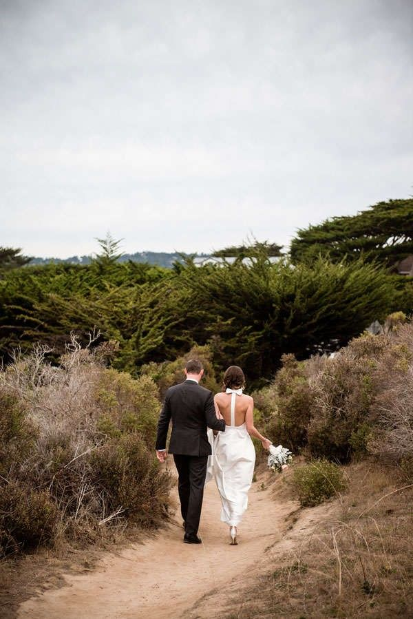 bride and groom walking along coast after California elopement
