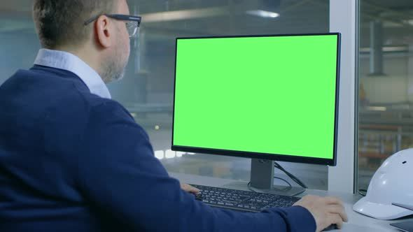 Chief Engineer Works On His Computer With MockUp Green Screen