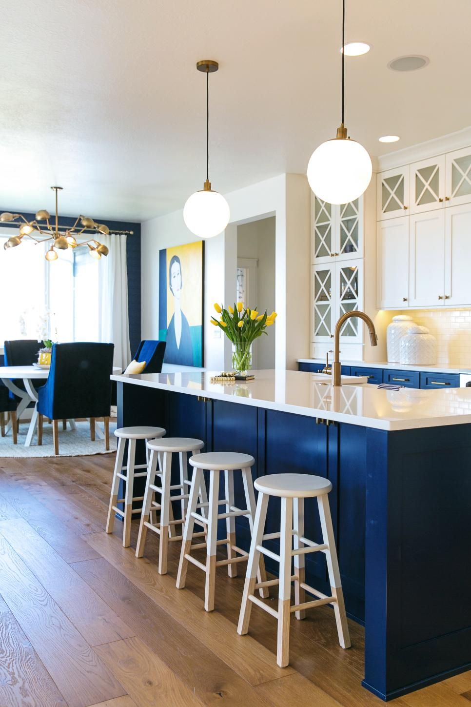 Blue and white kitchen with kitchen island stools and kitchen table with chairs