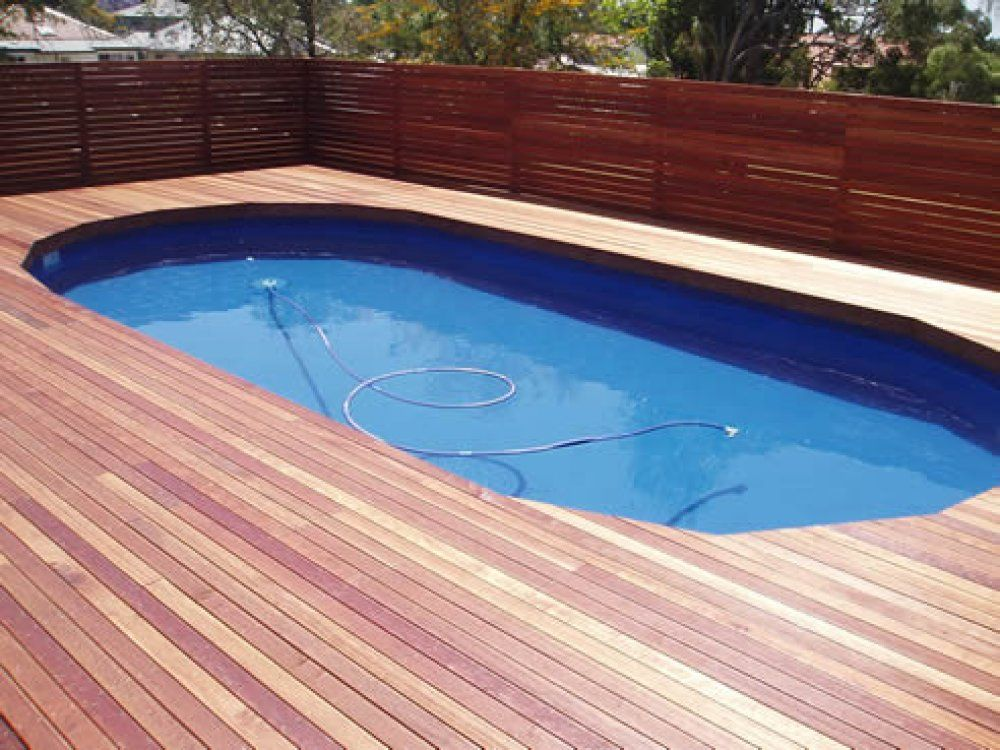 Here 39 s some timber decking around an inground swimming for Swimming pool deck